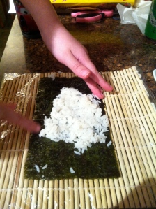 Big Kid places her rice on the nori.