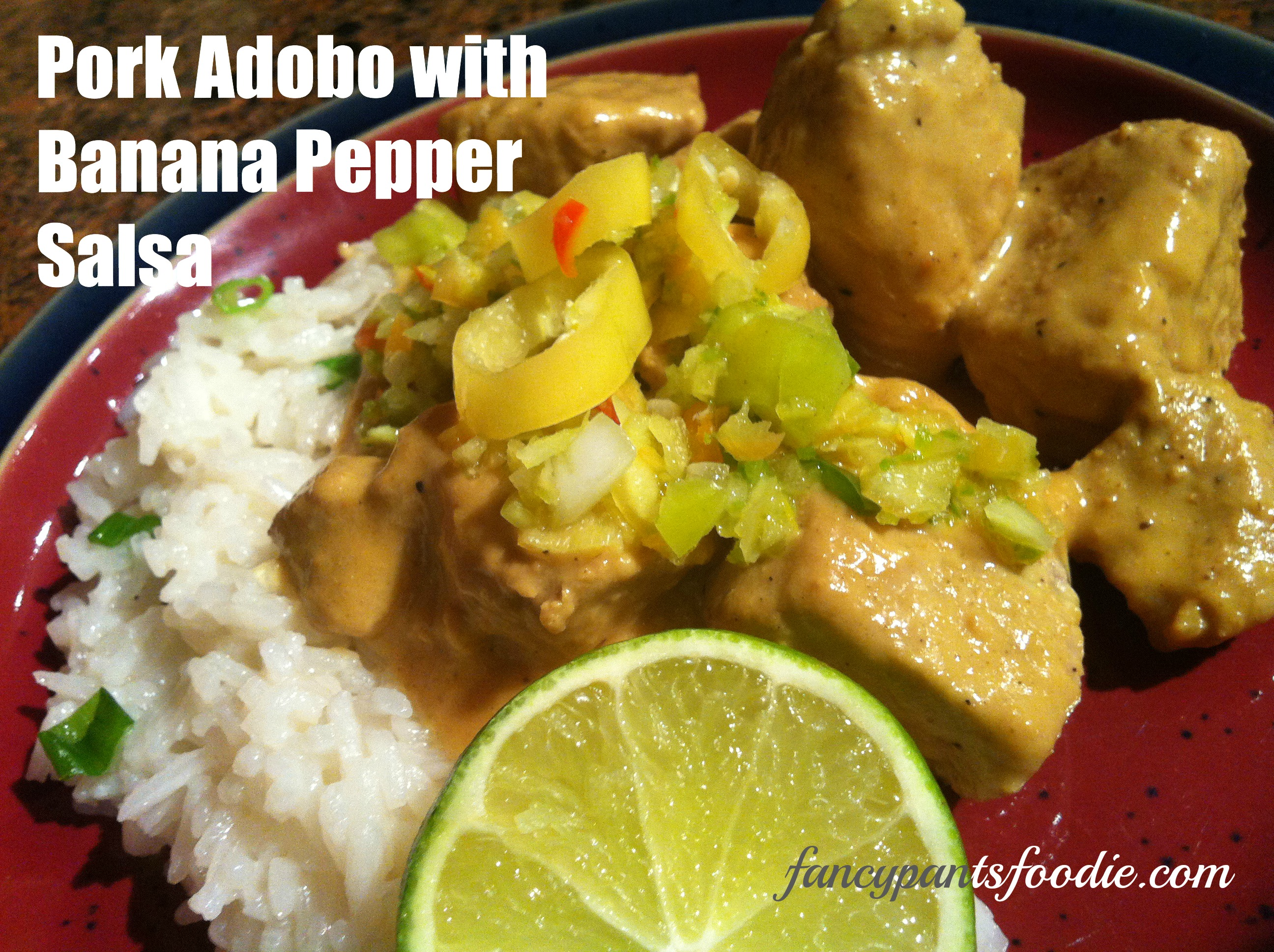 Photo of pork adobo with a salsa/relish made of green and yellow banana and other peppers, white rice with green onion, and a lime slice.