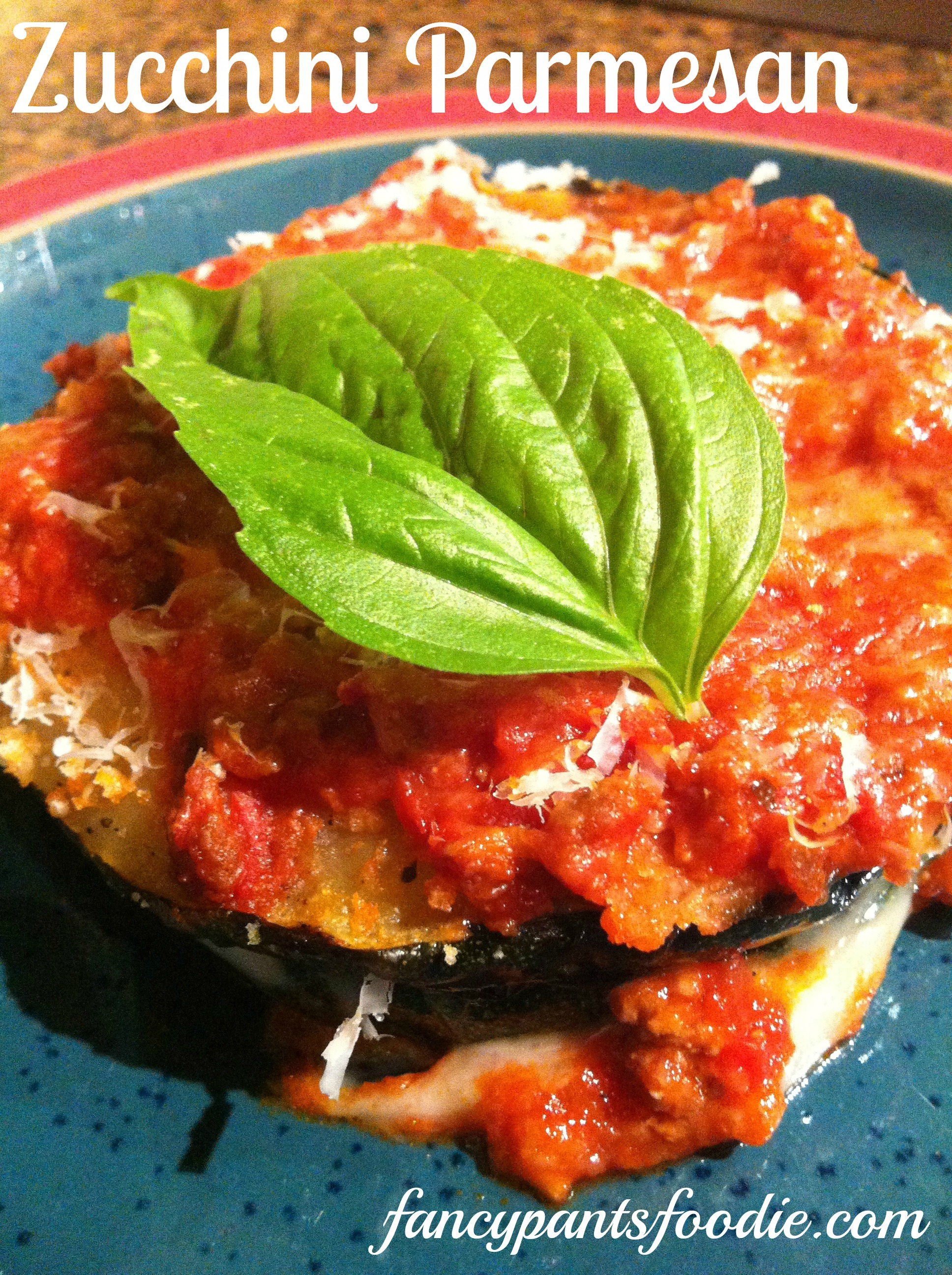 Overhead shot of zucchini parmesan with tomato sauce and freshly grated parmesan, garnished with basil leaf