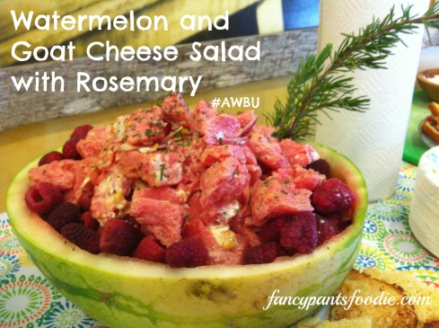Watermelon salad inside a hollowed watermelon half with rosemary sprig