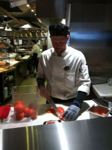 A chef slices tomatoes for the grill station.