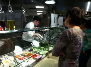A chef tosses a customer's salad to order at Green Leaf Grill.