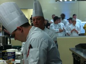 Chef Philippe Ducrot of Pulaski Tech (right) looks on as his sous works on a basket ingredient.