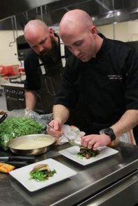 Chef Justin Patterson (right) and sous chef Daniel Rogers plating during the competition. The team won the preliminaries and will compete against Marc Guizol in the final on June 2.